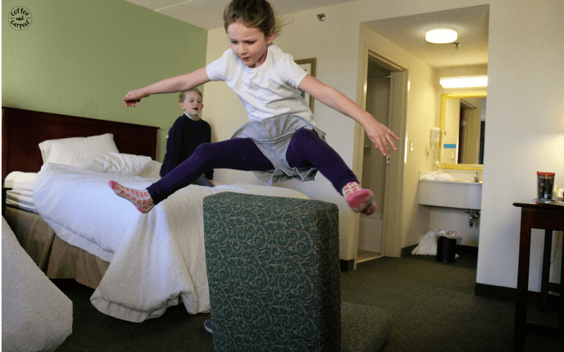 Create a jumping contest with couch cushions to entertain kids on family vacations during your hotel time #familyvacations #familytrip