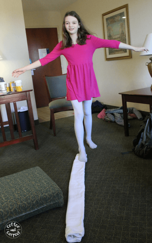 One simple way to entertain kids in a hotel on a family vacation is to fold a towel and make a balance beam. #familyvacations #familytrips
