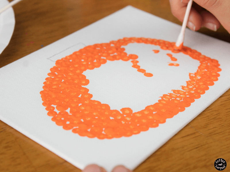 Filling in the pumpkin craft with orange dots